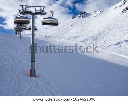 Ski lift and ski slope with skiers under it on sunny winter day with blue sky. Alpine resort Meribel, France. Europe, january, 2018 #1024621090