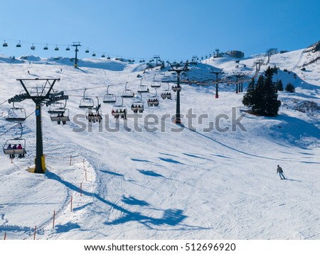 Ski lift and ski slope with skiers under it on sunny winter day with blue sky. Alpine resort Silvretta Arena near Samnaun and Ischgl, Switzerland and Austria, Alps, Europe #512696920