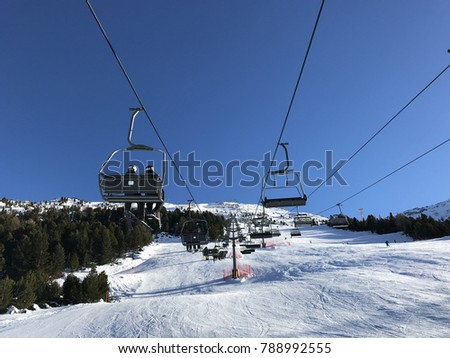 Ski lift and ski slope with skiers under it on sunny winter day with blue sky. Alpine resort  #788992555