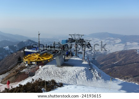 Ski lift at top of mountain-skiing descent - stock photo