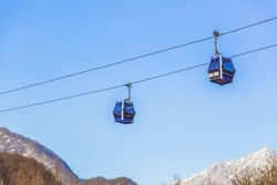 Ski lift cable, Ropeway, and cableway transport system for skiers with fog on valley background. High quality photo