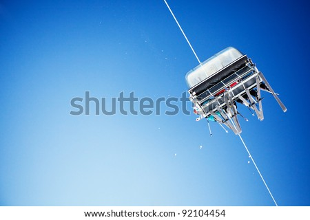 Ski lift carrying unrecognizable skiers up to the clear blue sky