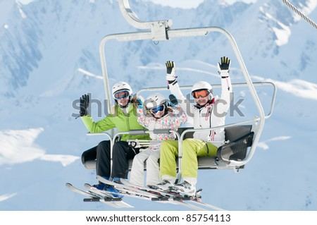 Ski lift - happy skiers in ski resort