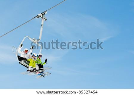 Ski lift - happy skiers on ski vacation (copy space)
