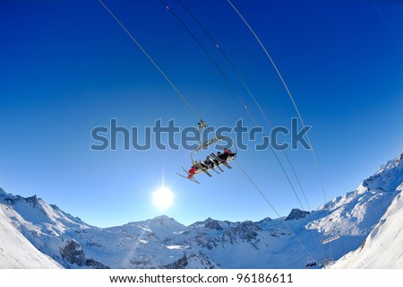 Ski lift - happy skiers use vertical transport  on ski vacation at sunny winter snow day
