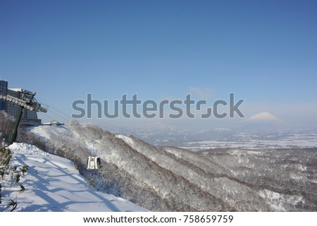 Ski lift in ski resort against winter landscape with a snow-covered volcano in background on Hokkaido island in northern Japan #758659759