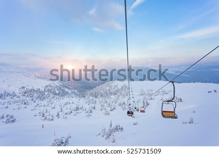 Ski lift with seats going over the mountain and paths from skies and snowboards #525731509