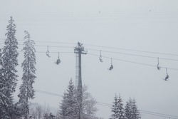 Ski lift with skiers and christmas trees. Part of the lift up the mountain, winter cloudy day with fog. Bukovel. Ukraine