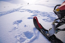 Ski of snowmobile and remote snowmobile silhouette in snowfield. Mountain pass and blizzard in   Khibiny Mountains,  Kola Peninsula, Russia -  Symbol  North and severe