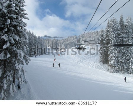 Ski piste and chair lift with snow covered trees on sunny day. Combloux ski area, French alps
