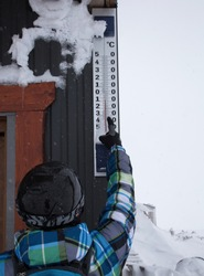 ski resort, a man skier in a helmet points to a large outdoor thermometer. On a scale of minus 8 degrees Celsius. Winter activity rest. Healthy lifestyle. Cold seasonal weather