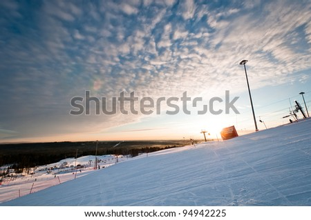 Ski resort big training slope at sunrise with tracks and trails - stock photo