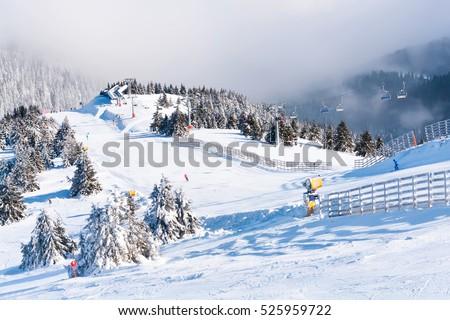Ski resort, ski slope, ski lift, pine trees and fog mountains panorama #525959722