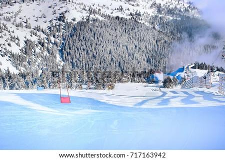 Ski resort, ski slope, ski lift, pine trees and fog mountains panorama #717163942