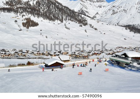 Ski scenario: Skiers approaching chairlift, mountains and village in the background - shot in Livigno, Italian Alps
