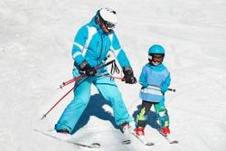 Ski school - little boy skiing with instructor