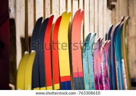 Ski shop sale. Rows of  colourful skis on wooden wall.  #763308610