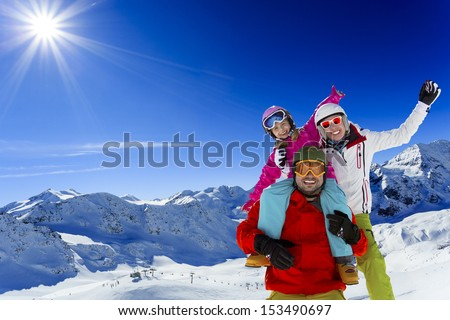 Ski, skier, sun and winter fun - family skiers  enjoying winter holidays
