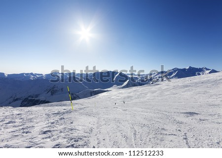 Ski slope and blue sky with sun. Caucasus Mountains, Georgia, ski resort Gudauri.