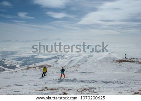 Ski slope. Armenia. 2 snowboarders travel on snow slopes. A Sunny day in the mountains of Tsakhkadzor.  #1070200625