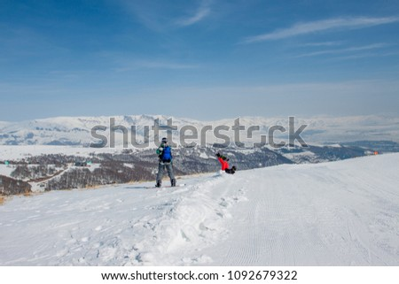 Ski slope. Armenia. 2 snowboarders travel on snow slopes. A Sunny day in the mountains of Tsakhkadzor.   #1092679322