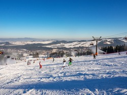 Ski slopes, chairlifts, skiers and snowboarders in Bialka Tatrzanska ski resort in Poland in winter. Snow cannons in action