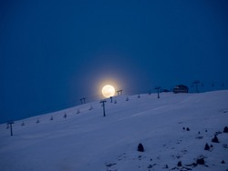 Ski slopes illuminated by the light of a giant moon. The moon rises from the top of the mountain. Monte Pora ski resort. Orobie. Italian Alps. Winter time