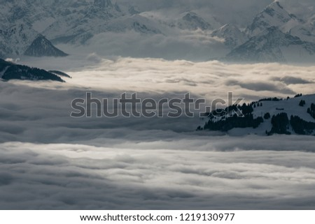 Ski slopes on the hills of Austrian Alps above clouds #1219130977