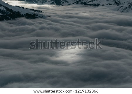 Ski slopes on the hills of Austrian Alps above clouds #1219132366