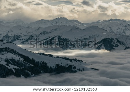 Ski slopes on the hills of Austrian Alps mountains above clouds #1219132360