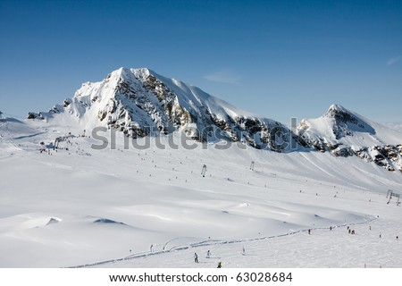 Ski slopes under high mountains in alp mountains