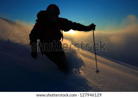 Ski tourer descending on skies at sunset, Tarcu mountains, Romania