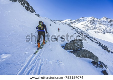Ski touring in high alpine landscape. Ascent and descent to a summit of an alpine peak. Snow and winter activities in mountains. #753159076