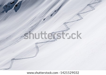Ski touring track leading up alpine mountain slope to ridge and pass in untouched powder snow in winter #1421529032