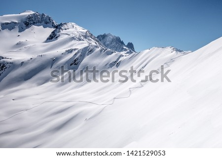 Ski touring track leading up alpine mountain slope to ridge and pass in untouched powder snow in winter