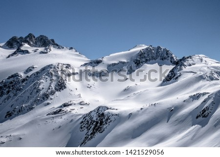 Ski touring track leading up alpine mountain slope to ridge and pass in untouched powder snow in winter #1421529056
