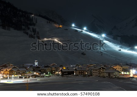 Ski village at night with slope lights, cross-country ski run, buildings, ice monument - shot in Livigno, Italian Alps