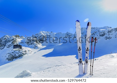 Ski winter season - mountains, cable car and ski equipments on ski run, cable car ski lift in background.