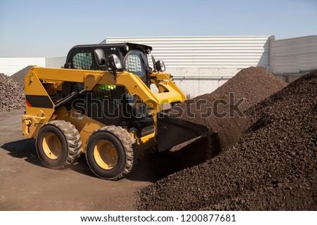 Skid loader or bobcat working on Manganese in Bulk ストックフォト ©