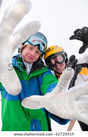 Skier and snowboarder in the snow posing for the camera