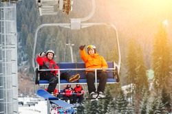 Skier and snowboarder riding up to the top of the mountain on ski lift and showing thumbs up gestures of good class, with an beautiful view nature. Bukovel, Ukraine