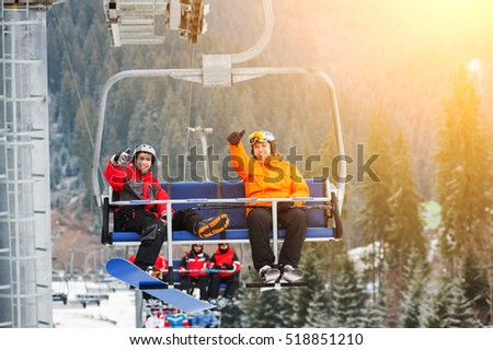 Skier and snowboarder riding up to the top of the mountain on ski lift and showing thumbs up gestures of good class, with an beautiful view nature. Bukovel, Ukraine #518851210
