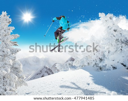 Skier at jump in Alpine mountains in beautiful sunny day. Copyspace for text #477941485