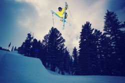 Skier Catching Big Air off jump at sunset