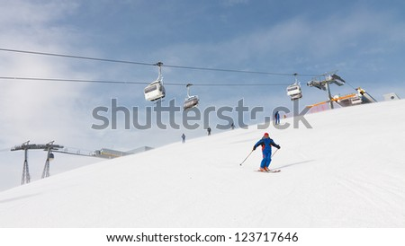 Skier cruising down the mountain near the summit of Kronplatz Ski Resort, South Tyrol, Italy.