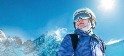 Skier female portrait in safe ski helmet and goggles with picturesque snowy Tatry mountains background. Active people winer vacation concept image.