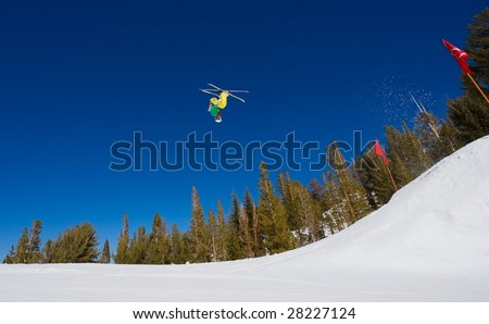 Skier Gets Big Air and does a Radical Backflip on A Sunny Day with Blue Sky #28227124