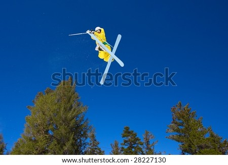Skier gets Big Air and Jumps Above Trees with Blue Sky