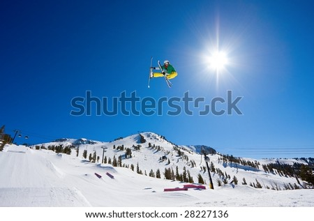 Skier Gets Radical Big Air with Sun and Blue Sky and Mountain In the Background - stock photo