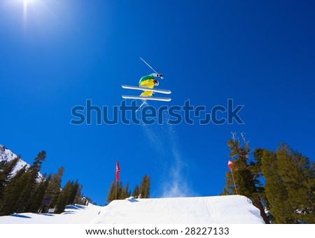 Skier goes off A Large Jump and Gets Big Air with Sun and Blue Sky